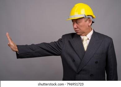 Studio shot of mature Asian businessman wearing hardhat against gray background