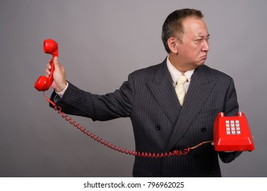 Studio shot of mature Asian businessman using old telephone against gray background