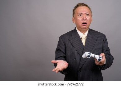 Studio shot of mature Asian businessman playing games against gray background