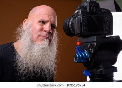 Studio shot of mature bald man with long gray beard against brown background