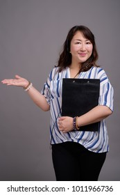 Studio shot of mature beautiful Asian businesswoman against gray background