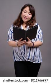 Studio shot of mature beautiful Asian businesswoman against gray background