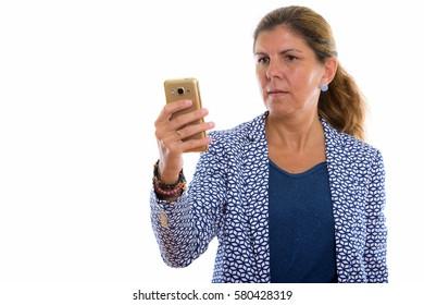 Studio shot of mature beautiful businesswoman using mobile phone