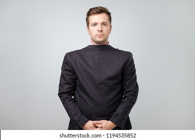 Studio shot of a mature caucasian man wearing his suit on backwards, gray background. He lost his mind from continuous work. Obvious mental problems