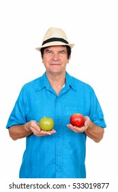 Studio shot of mature Caucasian man holding green and red apple isolated against white background
