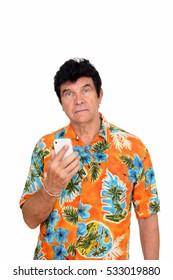Studio shot of mature Caucasian man wearing Hawaiian shirt holding mobile phone