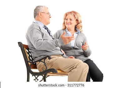 Studio shot of a mature couple talking to each other and smiling seated on a wooden bench isolated on white background