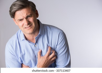 Studio Shot Of Mature Man Suffering Heart Attack