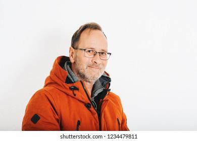 Studio shot of middle age man wearing orange winter jacket