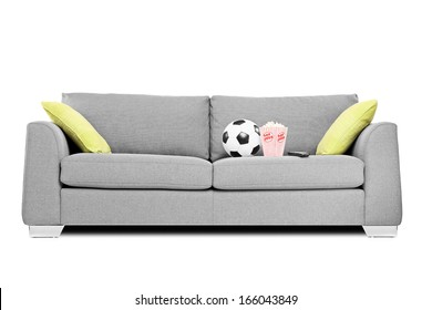 Studio shot of a modern couch with soccer ball and popcorn box on it isolated on white background