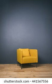 Studio shot of modern yellow arm-chair against of grey wall.Copy space.