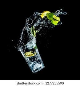 studio shot of mojito drink in freeze motion, flying lemon, lime, mint and ice in liquid splash against black background
