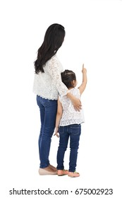 Studio shot of mother and daughter pointing at something, rear view