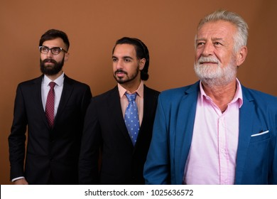 Studio shot of multi-ethnic bearded businessmen together against brown background