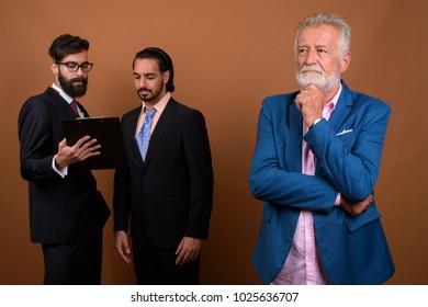 Studio shot of multi-ethnic bearded businessmen together against brown background