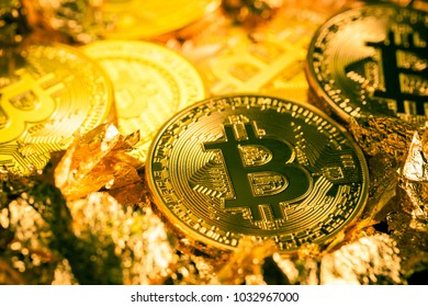 Studio shot of multiple bitcoin physical golden coins on a dark background with gold flakes. Bitcoin is a blockchain crypto currency