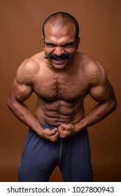 Studio shot of muscular Indian man with mustache shirtless against brown background