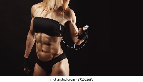 Studio shot of muscular young woman listening music on mobile phone against black background. Attractive blond bodybuilder with a mobile phone. Space for text on the right side