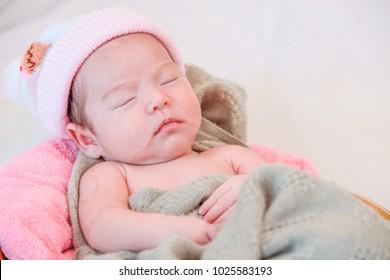 Studio shot of a newborn girl sleeping on large wooden bowl