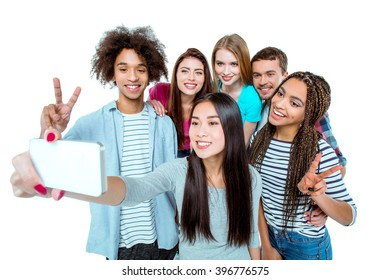 Studio shot of nice young multicultural friends. Beautiful people cheerfully smiling and having fun while making selfie photo on mobile phone. Isolated background