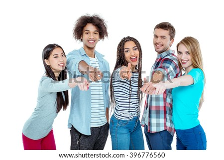 Studio shot of nice young multicultural friends. Beautiful people looking at camera, smiling and pointing at camera. Isolated background
