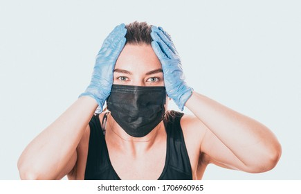 studio shot on white background of a sick young woman wearing mask and latex gloves, stressed by quarantine.