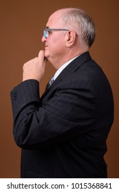 Studio shot of overweight senior businessman wearing eyeglasses against brown background