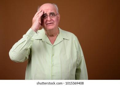 Studio shot of overweight senior man wearing eyeglasses against brown background