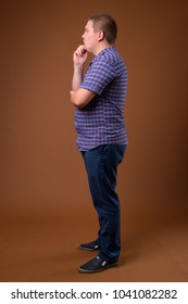 Studio shot of overweight young man wearing purple checkered shirt against brown background