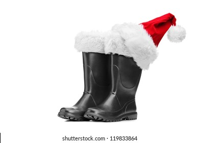 Studio shot of a pair of santa boots and santa hat isolated against white background