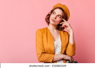 Studio shot of pensive french girl looking up. Charming young woman in beret thinking about something on pink background.