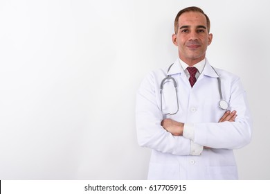 Studio shot of Persian man doctor with arms crossed against white background