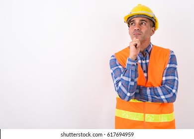 Studio shot of Persian man worker with hardhat thinking