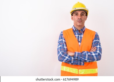 Studio shot of Persian man worker with hardhat arms crossed looking confident