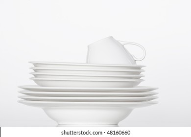 studio shot of a pile of white plates and white cup isolated on white