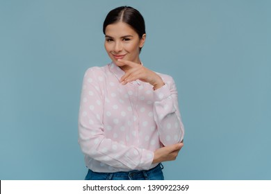 Studio shot of pleasant looking confident female touches chin gently with fore finger, dressed in polka dot shirt and jeans, wears minimal makeup, models over blue background. Human facial expressions