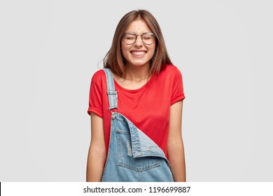 Studio shot of pleasant looking happy girl laughs positively, squints face, giggles from funny joke, expresses positiveness, dressed in casual red t shirt and dungarees, isolated over white background
