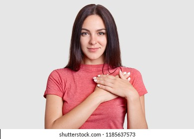 Studio shot of pleasant looking kind hearted young woman keeps hands on chest, expresses gratitude, dressed in casual t shirt, poses against white background, being thankful for help and support