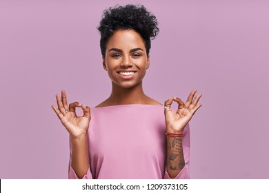 Studio shot of pleased young beautiful African American female shows ok sign, dressed in striped casual jacket, being in good mood, poses against lavender background. People and approval concept