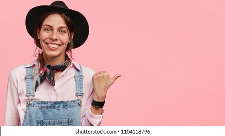 Studio shot of pleased young Caucasian female ranch worker has pleasant smile, rejoices success with selling products, indicates with thumb at blank pink wall for your promotional information.