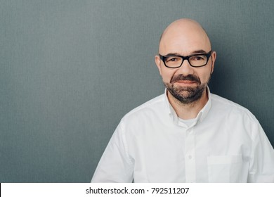 Studio shot portrait of a bald and bearded middle-aged man wearing eyeglasses while looking at camera with confidence against grey background