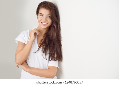 Studio shot portrait of a beautiful young woman looking at camera smiling thinking of an important decision or of a future plan