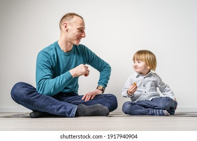 Studio shot portrait caucasian man sitting on the floor by small boy father and son eating biscuits while looking at each other happy having fun in front of white wall -family bonding and love concept
