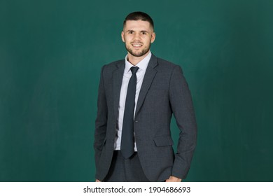 Studio shot portrait of a cute and elegant executive man in suit jacket standing and smile to the camera with self-confident on green screen.