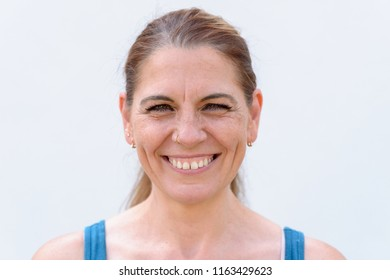 Studio shot portrait of a happy middle-aged woman smiling with confidence and positive thinking while looking at camera against gray background for copy space