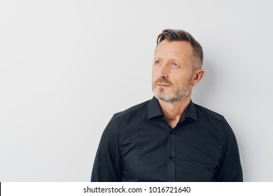 Studio shot portrait of a middle-aged creative man looking up while daydreaming about future against gray background for copy space