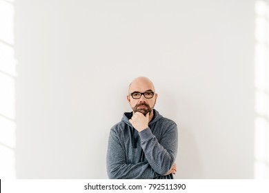 Studio shot portrait of a serious and undecided middle-aged man pondering while thinking of important decisions against gray background for copy space