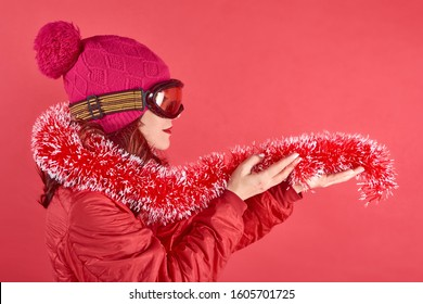 Studio shot portrait woman wearing rad ski clothes and standing in red background with tinsel and ski mask