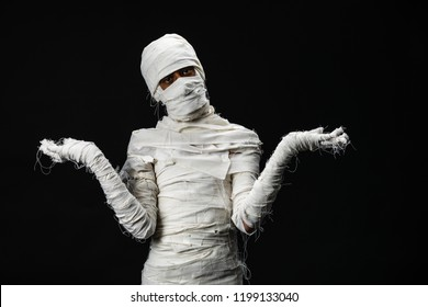 Studio shot portrait  of young man in costume  dressed as a halloween  cosplay of scary mummy pose like a open hand acting on isolated black background.