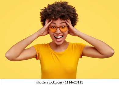 Studio shot of positive female reacts with great happiness on something pleasant, keeps hands on head, has broad smile, shows white teeth, wears casual t shirt, isolated over yellow background